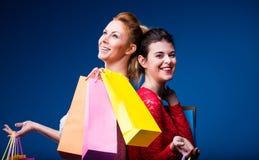 Frauen, die mit vielen Taschen auf Blau kaufen Lizenzfreie Stockfotografie