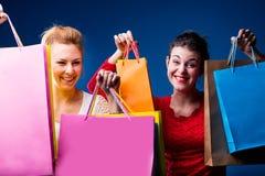 Frauen, die mit vielen Taschen auf Blau kaufen lizenzfreies stockbild