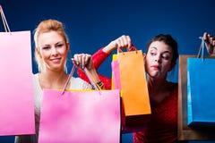 Frauen, die mit vielen Taschen auf Blau kaufen Stockbilder