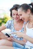 Frauen, die Mobiltelefon lachen und betrachten lizenzfreie stockfotos