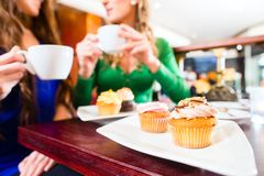 Frauen, die Muffins während Kaffeetrinken essen Lizenzfreie Stockfotos