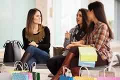 Frauen, die nach einem Tag des Einkaufens sich entspannen Stockbild