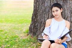 Frauen, die nahe großem Baum sitzen und in den Park zeichnen lizenzfreies stockbild