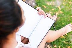 Frauen, die nahe großem Baum sitzen und in den Park zeichnen stockbilder