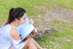 Frauen, die nahe großem Baum sitzen und in den Park zeichnen lizenzfreies stockfoto