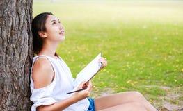 Frauen, die nahe großem Baum sitzen und in den Park zeichnen stockbild