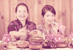 Frauen, die Pfannkuchen mit Kaviar während Shrovetide essen stockfotografie