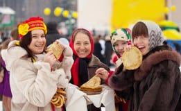 Frauen, die Pfannkuchen während Maslenitsa essen stockfotografie