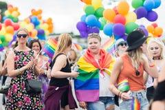 Frauen, die Regenbogenflaggen und -ballone während Stockholms Pride Parade halten Lizenzfreies Stockfoto