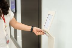 Frauen, die Schlüsselkartenzugriffskontrolle halten, um Aufzugsboden zu entriegeln und den Boden zu wählen Lizenzfreie Stockbilder