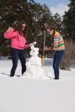 Frauen, die Schneemann aufbauen Stockfotos