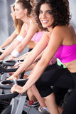 Frauen, die in spinnende Kategorie in der Gymnastik einen Kreislauf durchmachen Lizenzfreie Stockfotografie