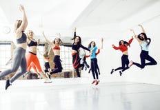 Frauen, die Sport in der Turnhalle, springend, Gesundheitswesenlebensstil-Leutekonzept, modernes Dachbodenstudio tun Stockfotos