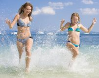 2 Frauen, die am Strand laufen Lizenzfreie Stockbilder