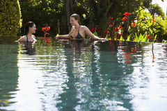 Frauen, die Swimmingpool im im Freien sprechen Stockfotografie