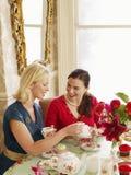 Frauen, die Tee an Speisetische trinken Lizenzfreies Stockfoto