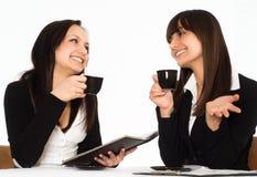 Frauen, die am Tisch sitzen stockbild