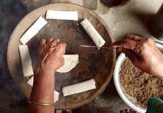 Frauen, die traditionellen Kuchen Bora Pitha des Assamese vorbereiten Lizenzfreies Stockbild