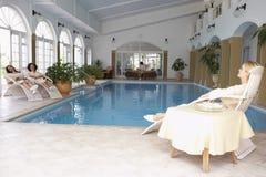 Frauen, die um Pool am Badekurort sich entspannen Stockfotos