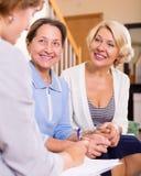 Frauen, die am Versicherungsagenten sich beraten Stockfotografie