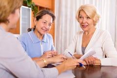 Frauen, die am Versicherungsagenten sich beraten Stockbilder