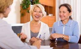 Frauen, die am Versicherungsagenten sich beraten Lizenzfreie Stockfotos