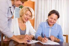 Frauen, die am Versicherungsagenten sich beraten Stockfotos