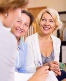 Frauen, die am Versicherungsagenten sich beraten Stockbild