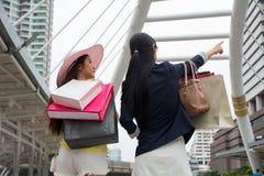Frauen, die vorwärts das Wochenendeneinkaufen und -blick zum folgenden sho genießen stockbild