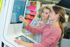 2 Frauen, die wechselwirkenden Kiosk verwenden lizenzfreie stockbilder