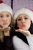 Frauen, die Weihnachtskuß geben Stockfoto