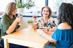 Frauen, die Wein am Restaurant sprechen und trinken stockbild