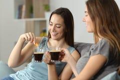 Frauen, die werfenden Zucker des Kaffees in Schale trinken stockbild