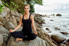 Frauen, die Yoga mit dem Ozean hinten tun Lizenzfreies Stockbild
