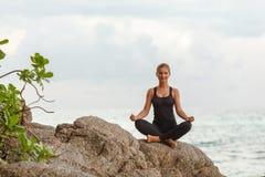 Frauen, die Yoga mit dem Ozean hinten tun Lizenzfreie Stockfotografie