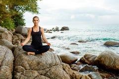 Frauen, die Yoga mit dem Ozean hinten tun Lizenzfreie Stockfotos