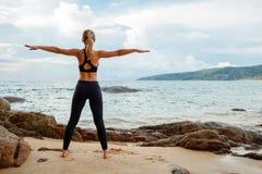 Frauen, die Yoga mit dem Ozean hinten tun Stockfoto