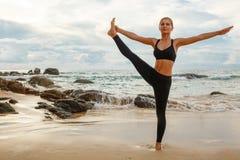 Frauen, die Yoga mit dem Ozean hinten tun Stockbild