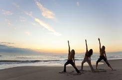 Frauen, die Yoga am Strand-Sonnenaufgang oder dem Sonnenuntergang üben Stockfotos