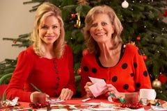 Frauen, die zu Hause Weihnachtskarten bilden Stockbilder