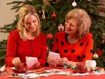 Frauen, die zu Hause Weihnachtskarten bilden Stockfotos