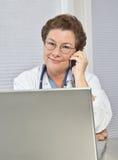 Frauen-Doktor am Computer, sprechend am Telefon Lizenzfreie Stockfotografie