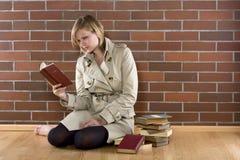 Frauen in einem trenchcoat liest Buch Stockbild