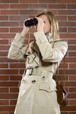 Frauen in einem trenchcoat mit Binokeln Stockfotografie