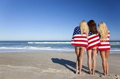 Frauen eingewickelt in den amerikanischen Flaggen auf einem Strand Stockfotografie
