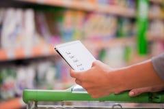 Frauen-Einkaufen mit Checkliste und Laufkatze Lizenzfreies Stockbild