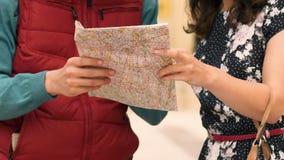 Frauen-Entdeckungsweise des Mannes helfende zum Hotel, Richtung auf Kartennahaufnahme zeigend, Tourismus stock footage