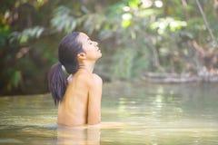 Frauen entspannen sich, ein Bad im Wald nehmend stockbild