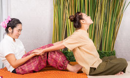 Frauen erhält ihren Arm ausgedehnt durch thailändische Massage stockfoto