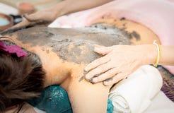 Frauen erhält Lehm sich scheuern an zurück im Badekurort stockfotos
